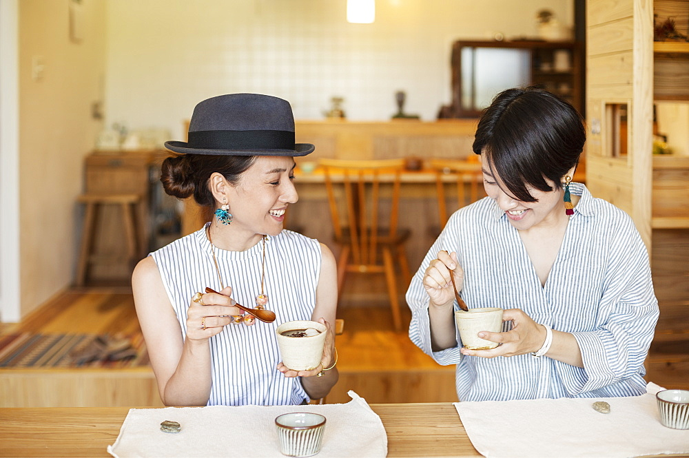 Two smiling Japanese women eating in a vegetarian cafe, Kyushu, Japan