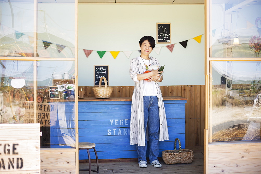 Japanese woman standing in a farm shop, holding vegetables, smiling at camera, Kyushu, Japan