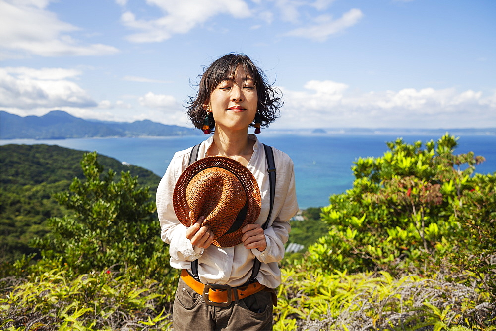 Japanese woman holding hat standing on a cliff, ocean in the background, Kyushu, Japan