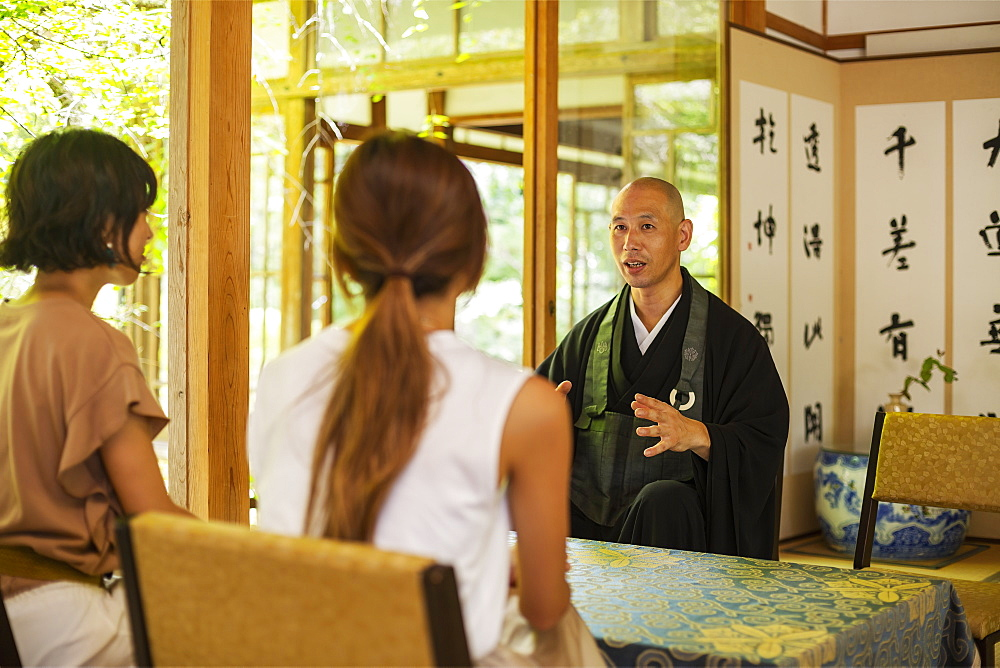 Two Japanese women and Buddhist priest kneeling in Buddhist temple, talking, Kyushu, Japan