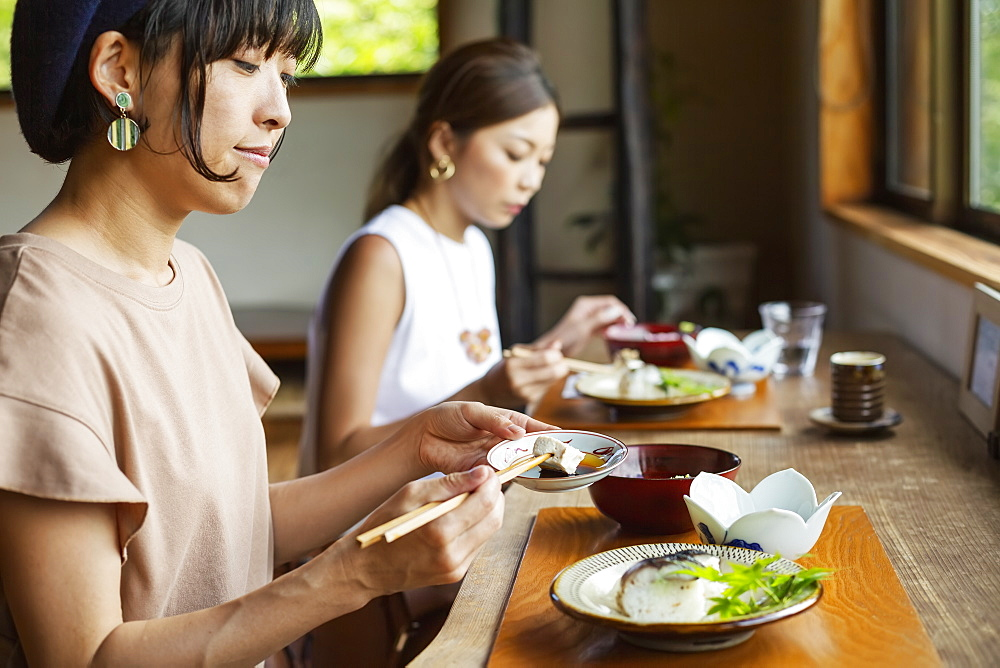 Two Japanese women sitting at a table in a Japanese restaurant, eating, Kyushu, Japan