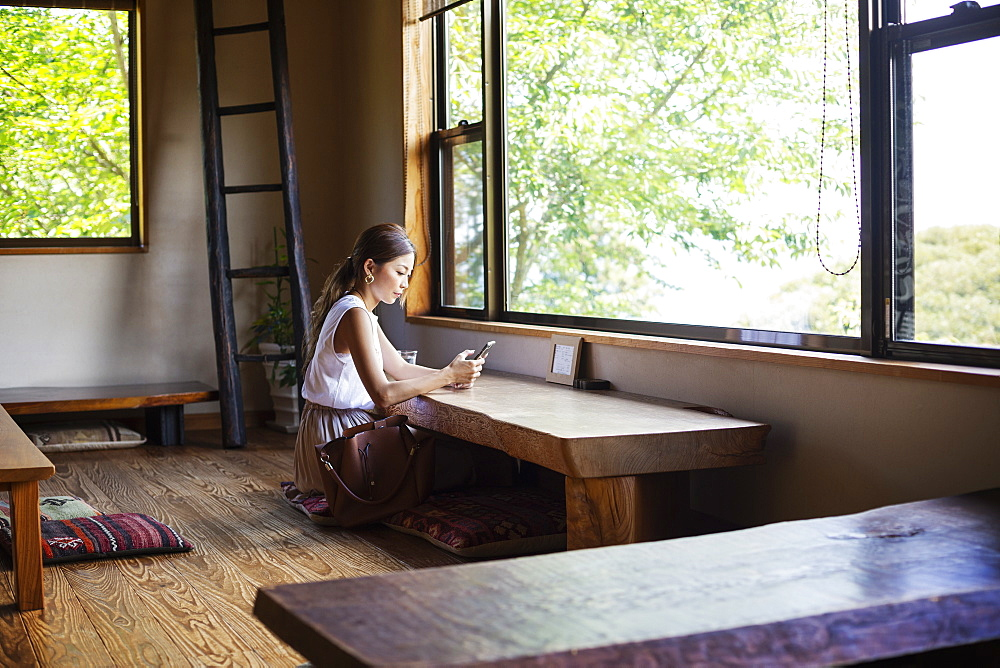 Japanese woman sitting at a table in a Japanese restaurant, Kyushu, Japan