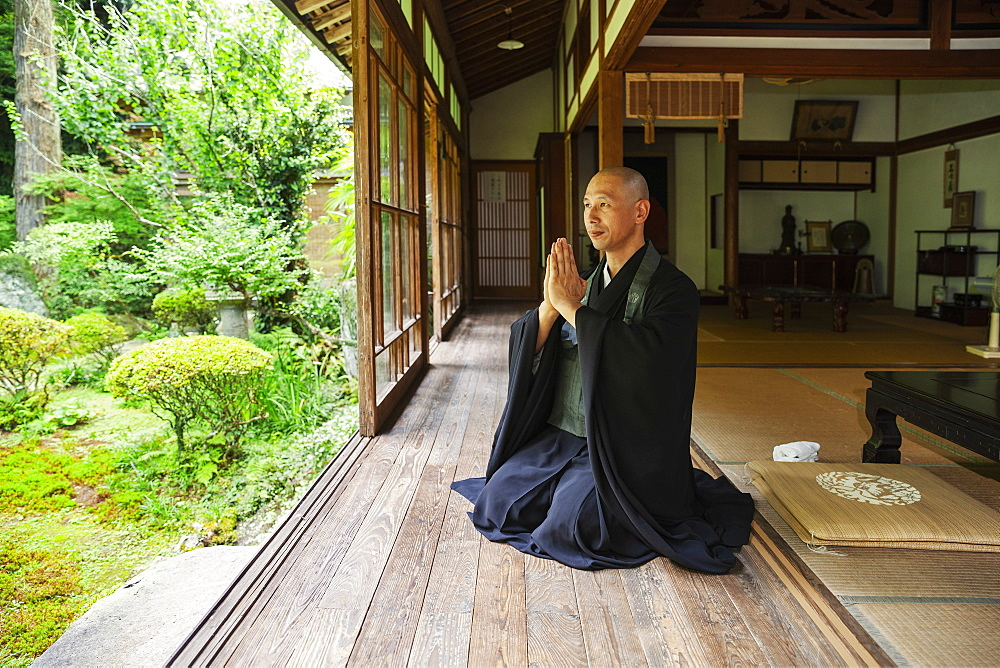 Buddhist priest kneeling in Buddhist temple, praying, Kyushu, Japan