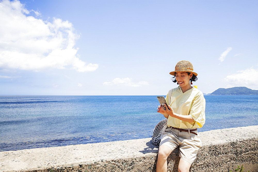 Japanese woman wearing hat sitting on a wall, ocean in the background, Kyushu, Japan