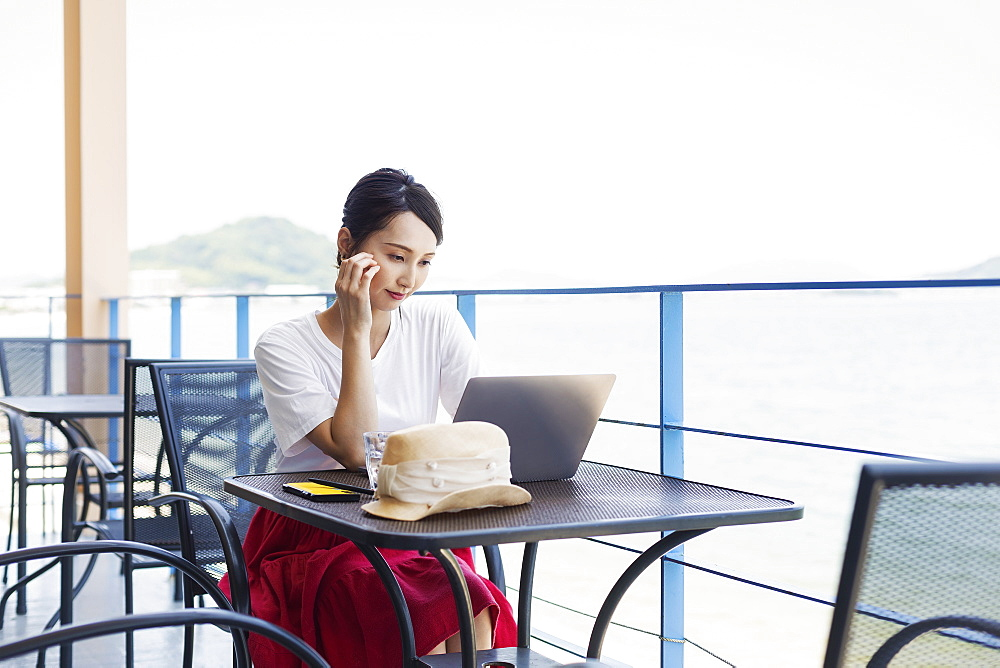 Female Japanese professional sitting on balcony of a co-working space, using laptop computer, Kyushu, Japan