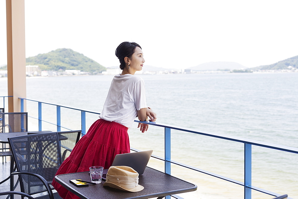 Female Japanese professional standing on balcony of a co-working space, laptop computer on table, Kyushu, Japan