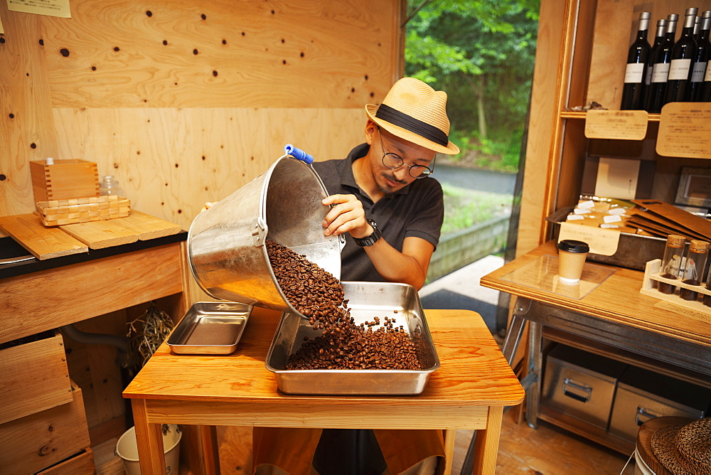 Japanese man wearing hat and glasses sitting in an Eco Cafe, pouring freshly roasted coffee beans into metal tray, Kyushu, Japan