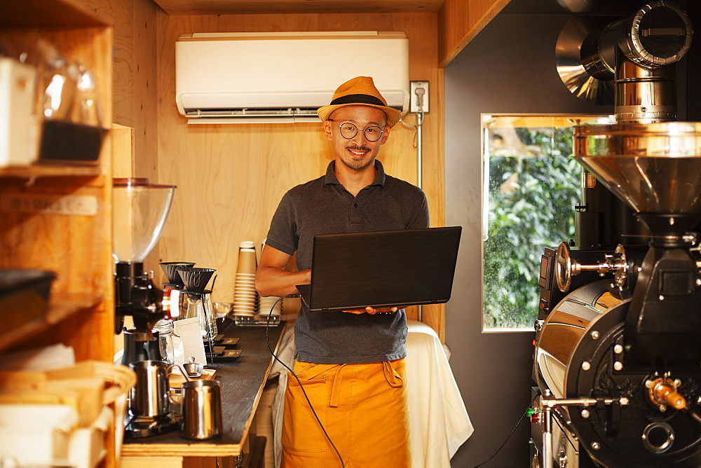 Japanese man wearing hat and glasses standing in an Eco Cafe, holding laptop computer, smiling at camera, Kyushu, Japan