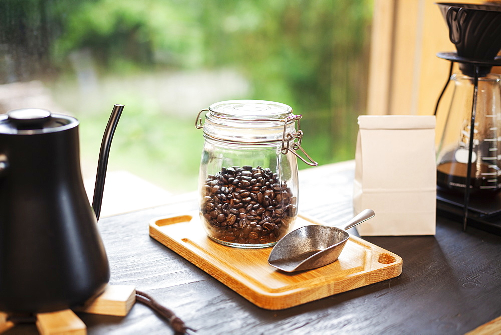 Close up of coffee pot, glass jar with coffee beans and metal coffee shovel on wooden board, Kyushu, Japan