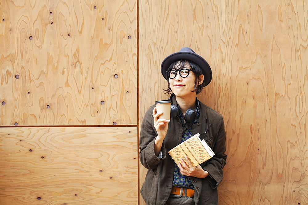 Japanese woman wearing glasses and hat standing outside Eco Cafe, holding paper cup and notebook, Kyushu, Japan