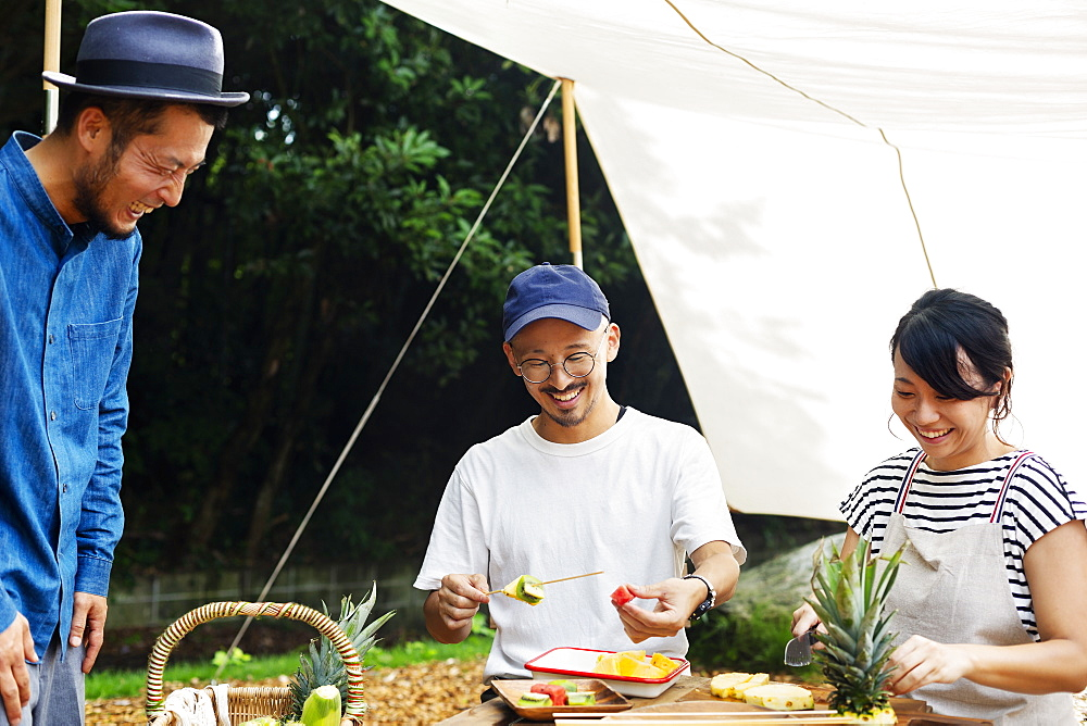 Two Japanese men and woman gathered around a table under a canopy, preparing fresh fruit, Kyushu, Japan