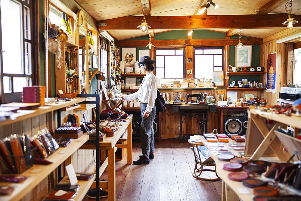 Japanese woman browsing merchandise in a leather shop, Kyushu, Japan