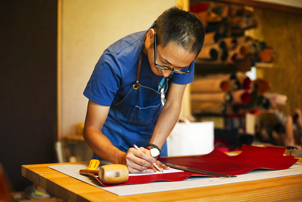 Japanese man wearing blue apron working in a leather shop, Kyushu, Japan