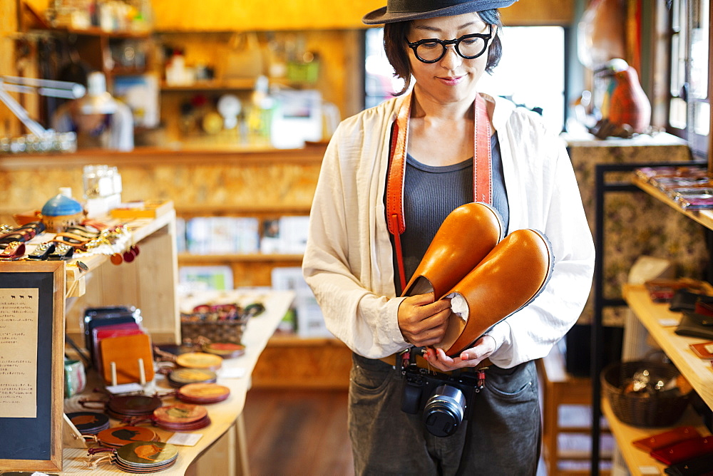 Japanese woman wearing hat and glasses standing in a leather shop, holding pair of leather shoes, Kyushu, Japan