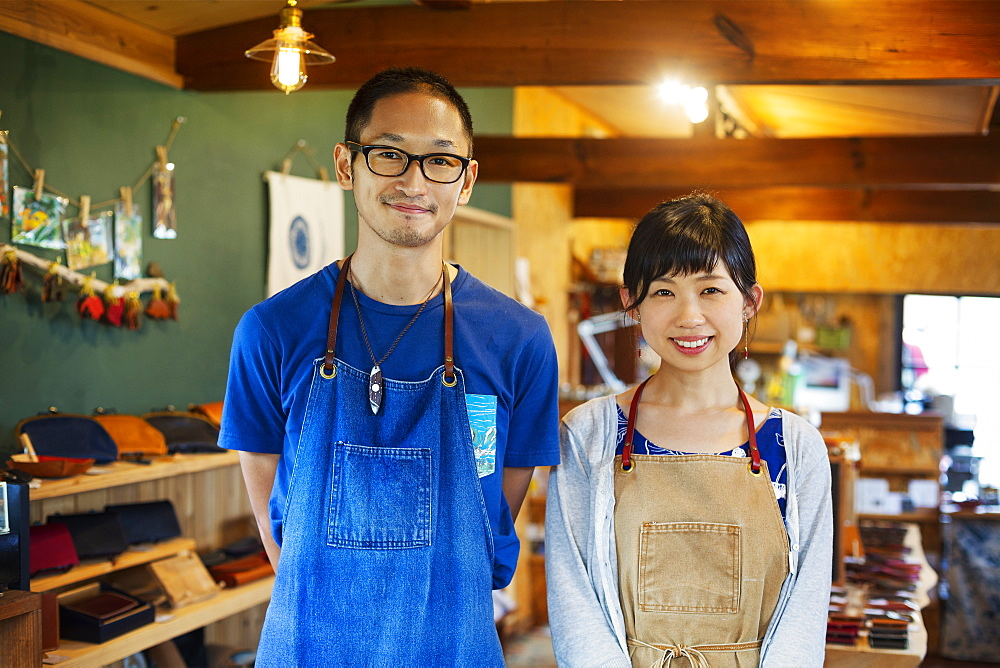 Japanese woman and man wearing blue apron standing in a leather shop, smiling at camera, Kyushu, Japan