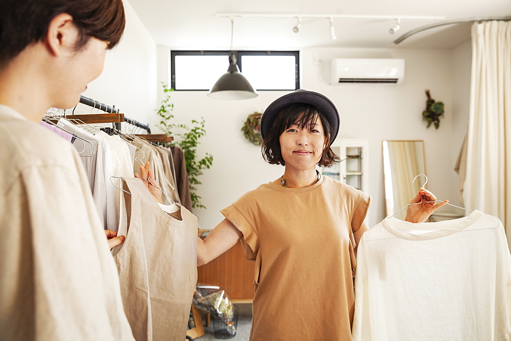 Two Japanese women standing in a small fashion boutique, looking at tops, Kyushu, Japan