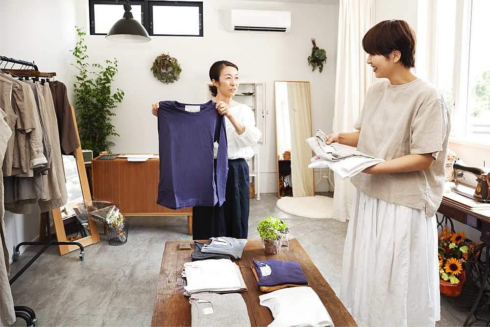 Two Japanese women standing in a small fashion boutique, arranging T-Shirts on a coffee table, Kyushu, Japan
