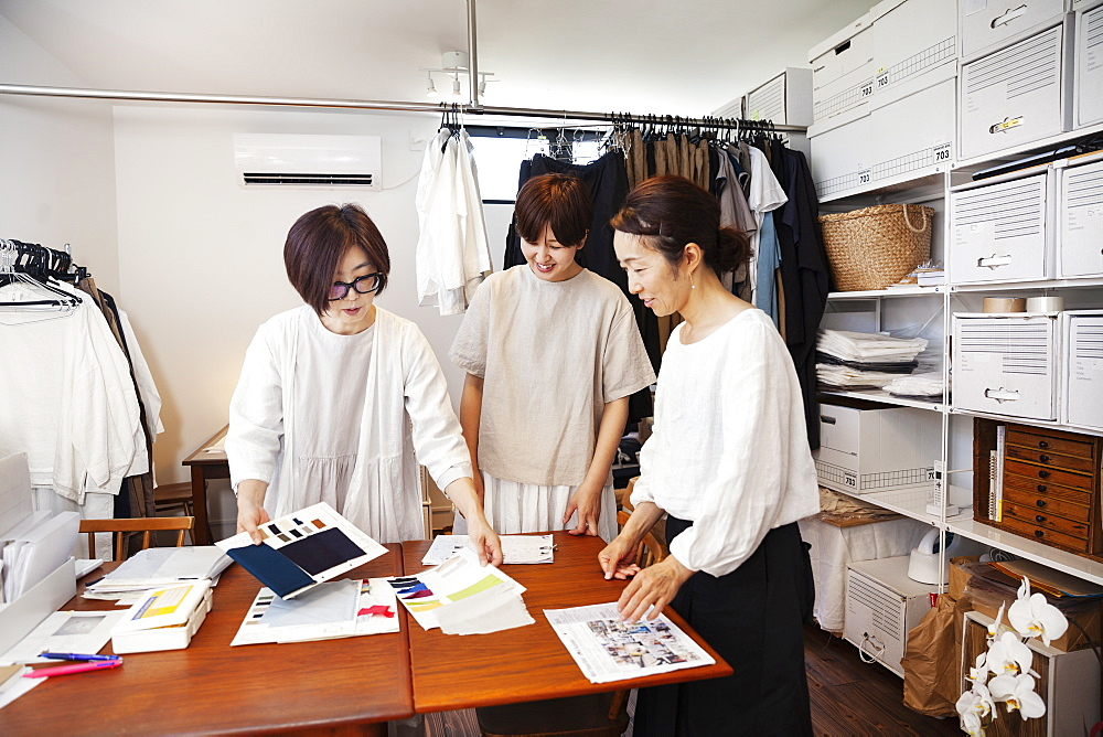Three Japanese women standing at a table in a small fashion boutique, looking at fabric samples, Kyushu, Japan