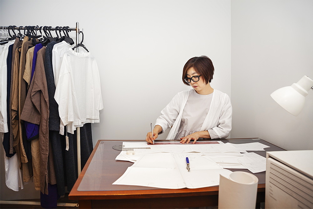 Japanese woman wearing glasses working at a desk in a small fashion boutique, Kyushu, Japan