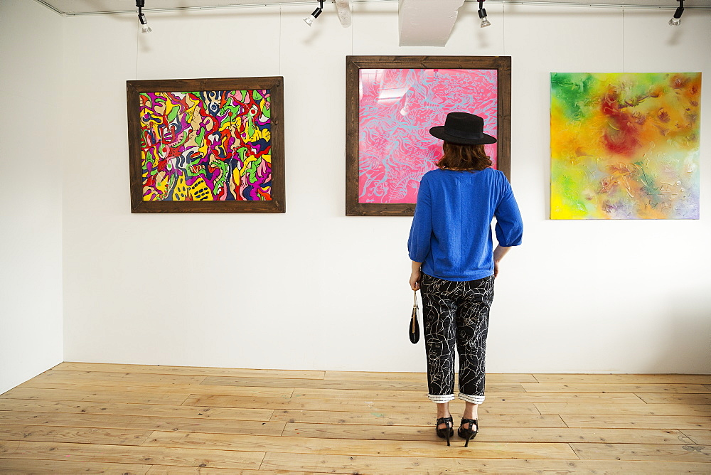 Japanese woman wearing hat standing in front of abstract painting in an art gallery, Kyushu, Japan