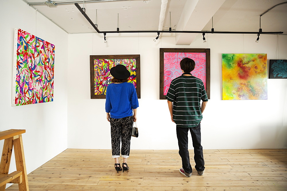 Rear view of Japanese man and woman looking at abstract painting in an art gallery, Kyushu, Japan