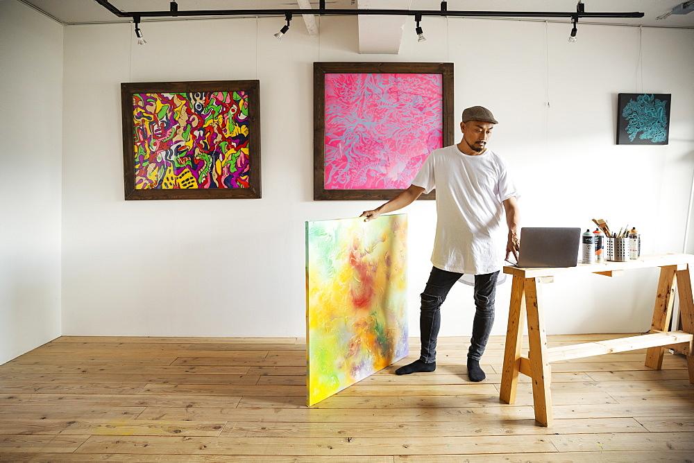 Japanese man standing in art gallery, holding abstract artwork, looking at laptop computer, Kyushu, Japan