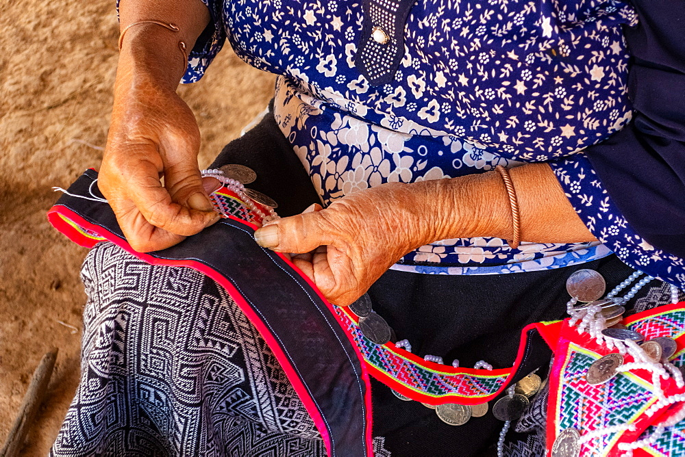 Woman seated stitching, making traditional garments, Vang Vieng, Laos, Laos