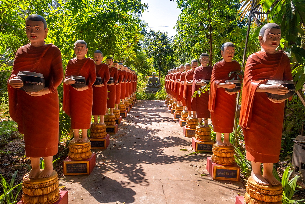 Row of Buddhist monk statues with red robes and alms bowls in the gardens of the Buddhist Temple at Siem Reap, Cambodia