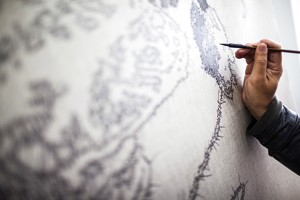 Close up of artist at work on a new painting in a studio, China