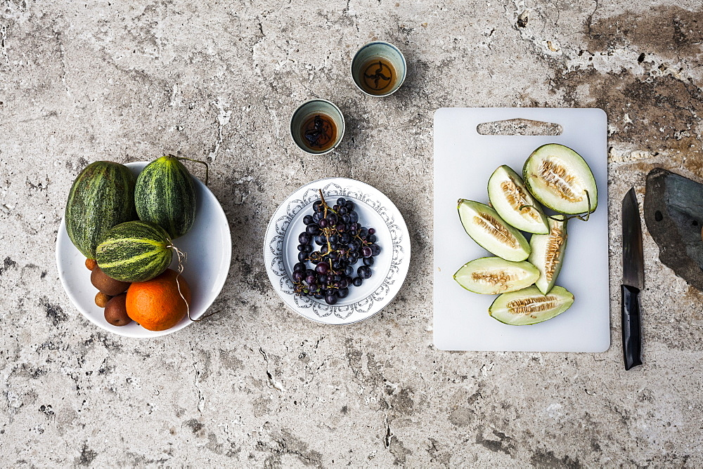 High angle close up of a stone table, with tea and selection of fresh fruits on plates and cutting board, China
