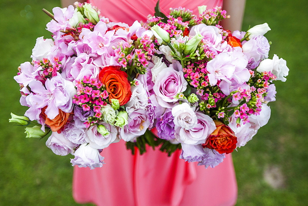 High angle close up of woman holding two bouquets of flowers with pink roses