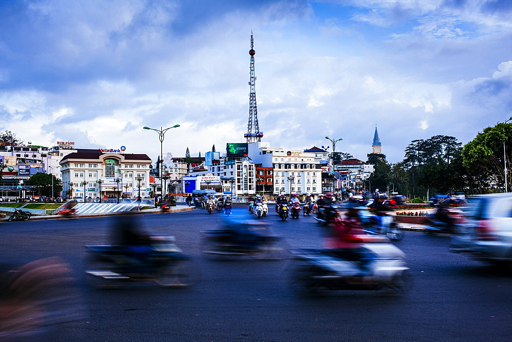 Urban scene with blurred motion of passing traffic and motorbikes on wide street, Vietnam