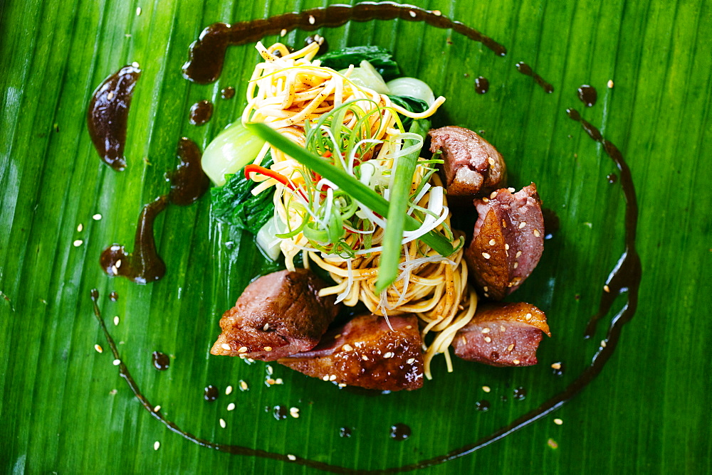 High angle view of seared duck breast and noodles served on a banana leaf, Vietnam
