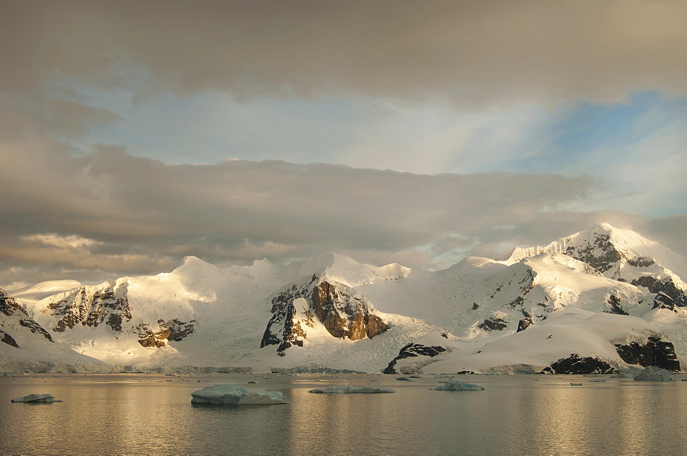 Dusk and flat calm water off the shore of a mountain landscape in Antarctica, Antarctic mountains, Antarctica