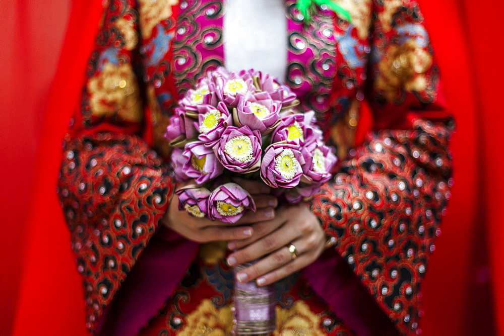 Close up of young Vietnamese bride wearing a colourful robe, holding a bouquet of lotus flowers, Vietnam, Mekong Delta