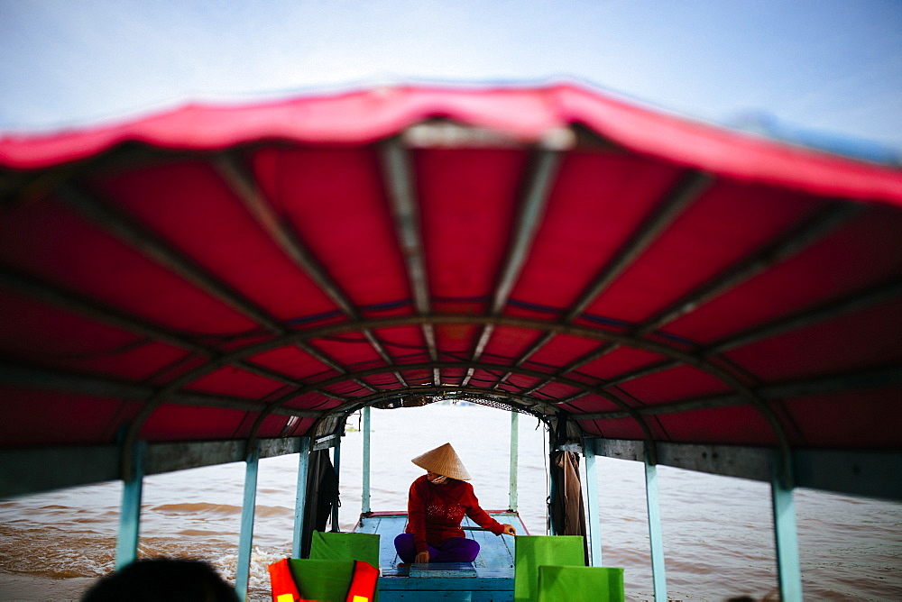 Woman piloting a boat with red canopy through a river, Vietnam, Mekong Delta