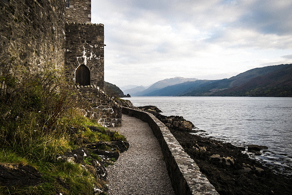 Castle in wall overlooking a loch with mountains in the distance, Scotland