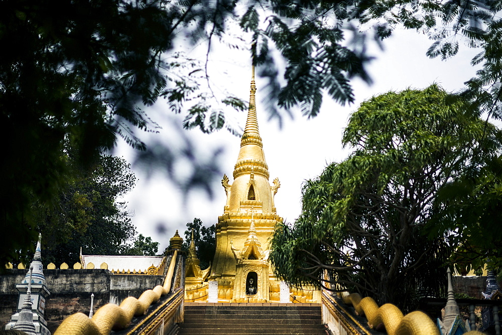 Exterior view of small local temple with golden stupa, Thailand