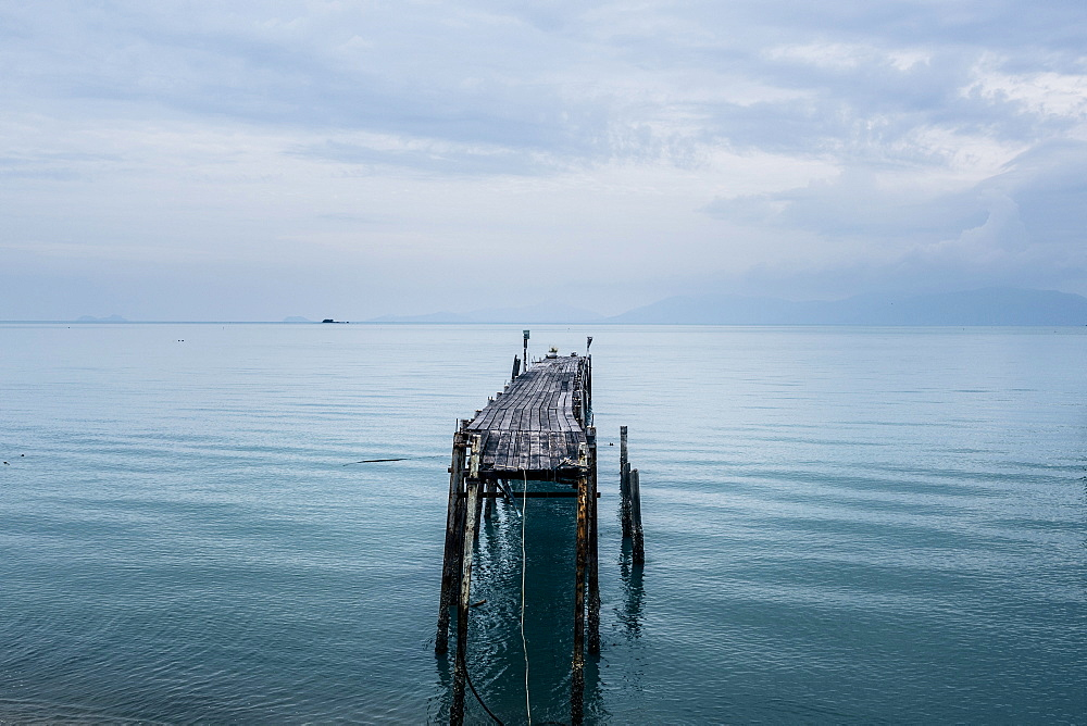 Seascape with old wooden jetty under a cloudy sky, Thailand