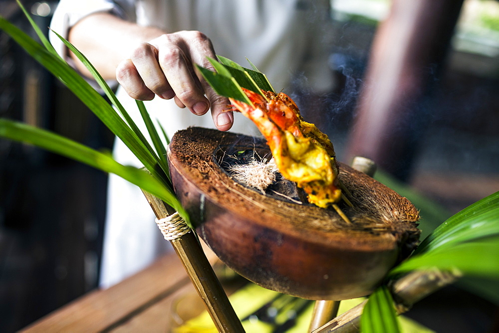 Close up of chef preparing charcoal-grilled prawn satay on a coconut shell, Thailand