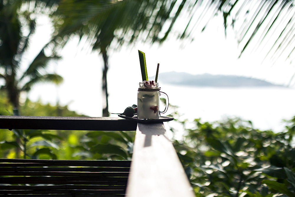 "Close up of a ""Tom Yum"" cocktail with coconut-infused liquour standing a balustrade of balcony, Thailand"