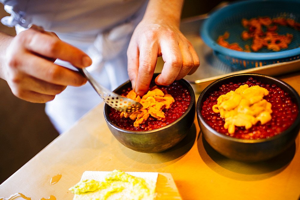 High angle close up of chef preparing uni, sea urchin, with salmon roe and rice, Japan