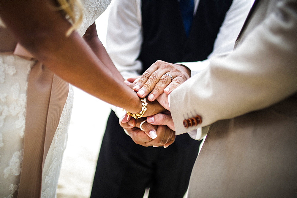 Close up of a husband and wife joining hands during the ceremony at a beach, Thailand
