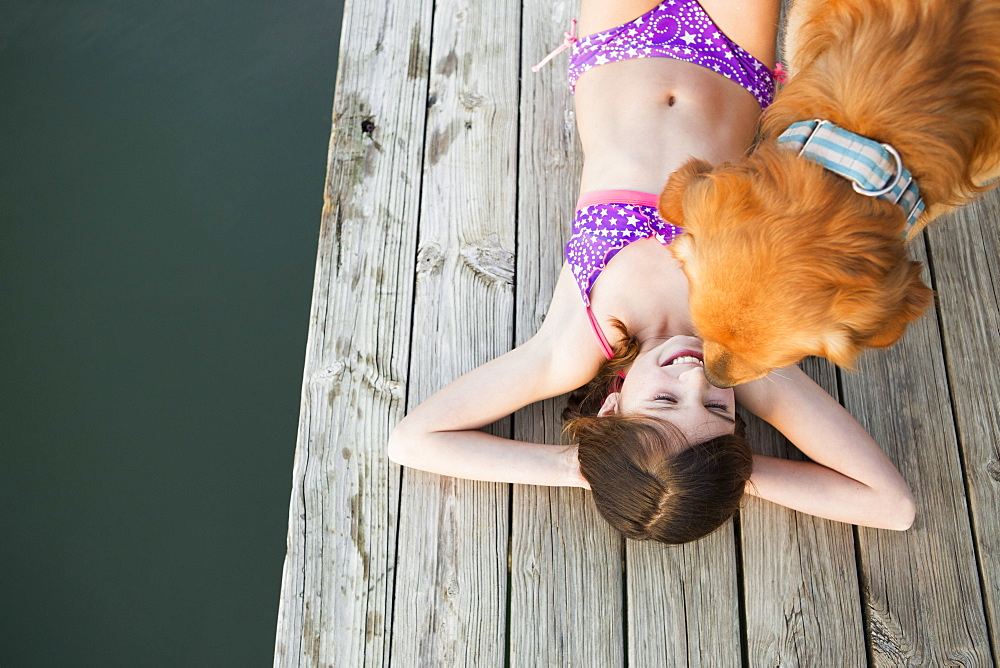A young girl and a golden retriever dog on a jetty, Austin, Texas, USA