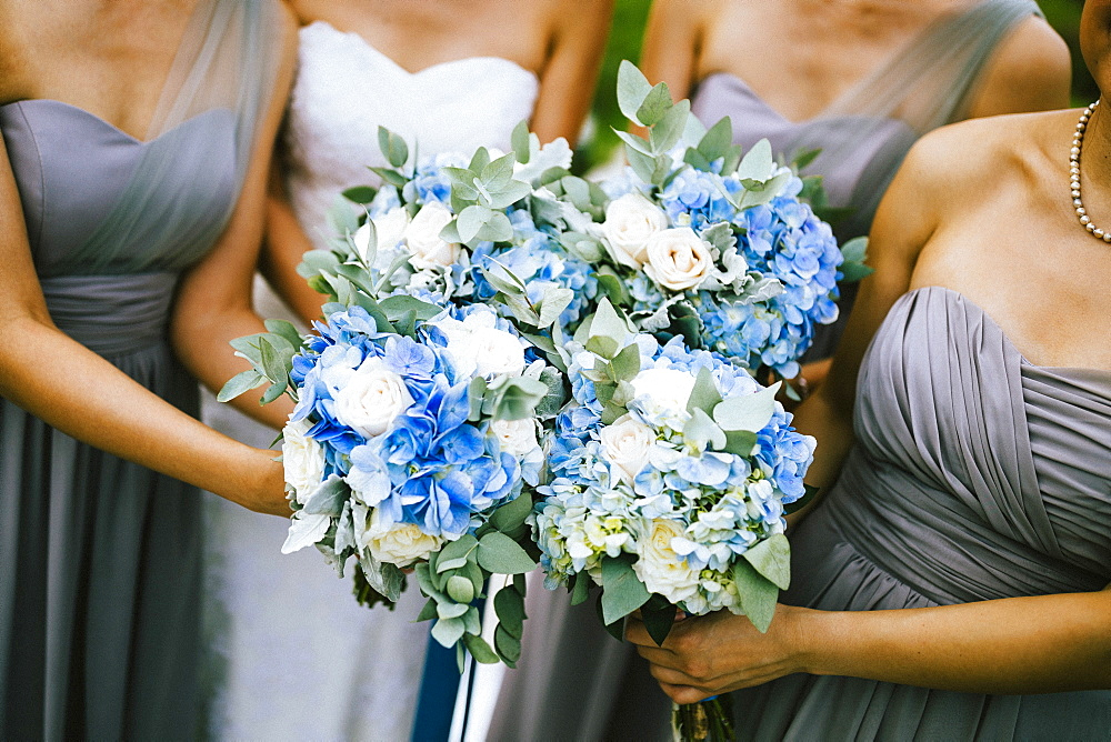 High angle view of bride and bridesmaids holding blue and white flower bouquets, Thailand