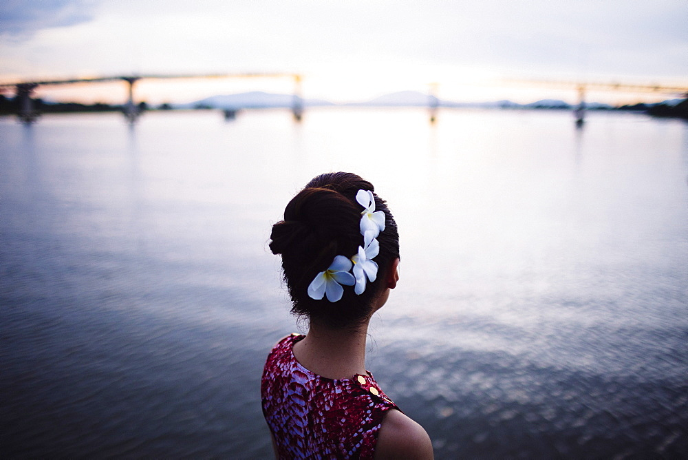 Rear view of woman with flowers in her hair, standing by the sea at sunset, bridge in the distance, Vietnam
