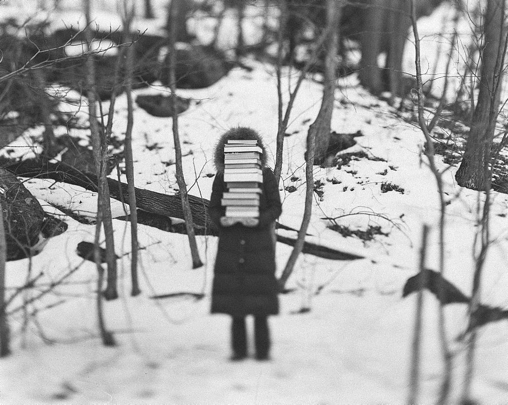 Child wearing a coat standing in a winter forest, holding a tall stack of books