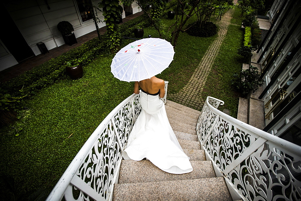 High angle view of young bride walking down an ornate staircase, Vietnam