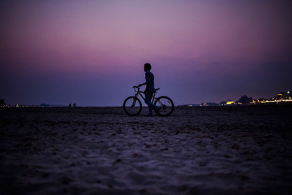 Silhouette of boy pushing a bicycle on the banks of a river at sunset