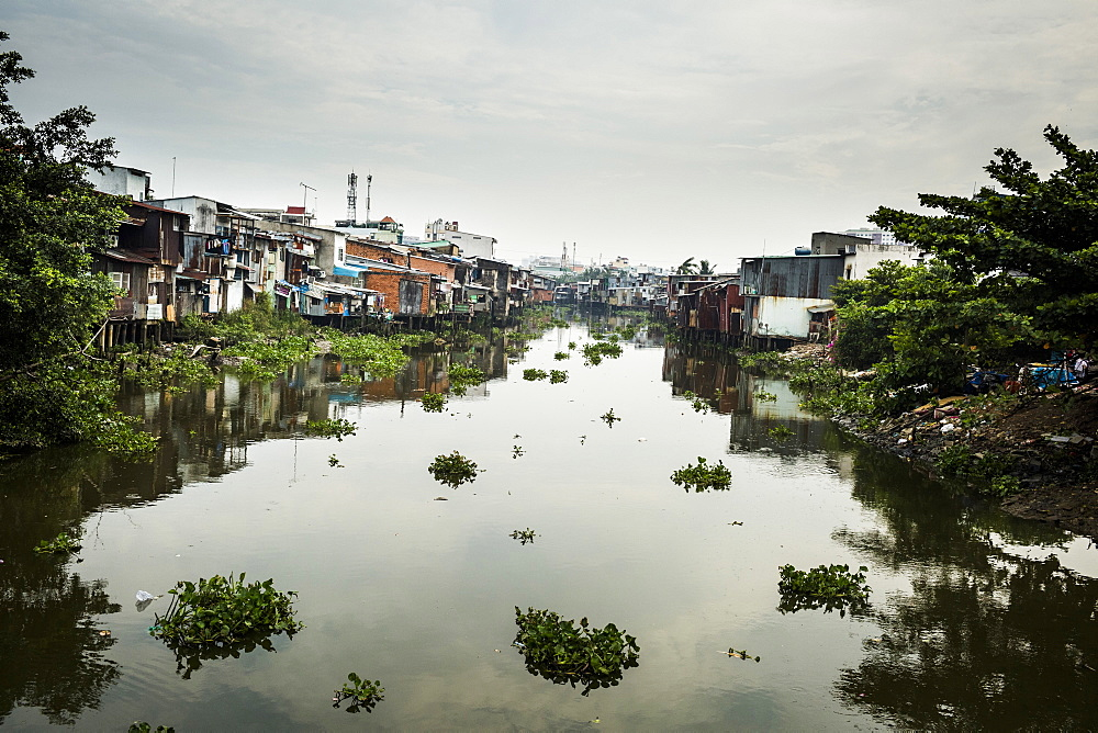 View along small canal with houses built onto the water, Vietnam